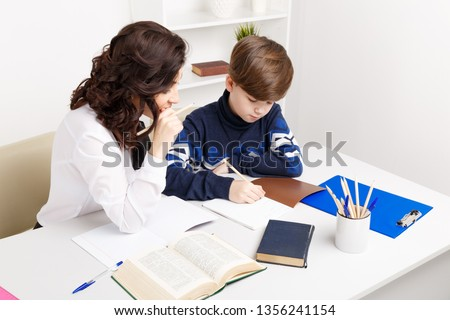 Female teacher helps teen boy to do his homework. Doing homework together. #1356241154