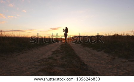 A business woman walks along a country road with a tablet in her hand, the sun miertsaet between women's legs. sexy business woman girl running in the countryside. sexy girl travels in countryside #1356246830