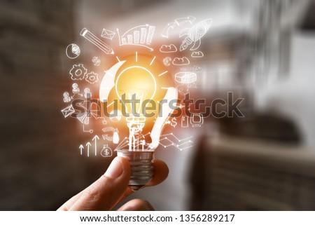 Hand holding light bulb #1356289217