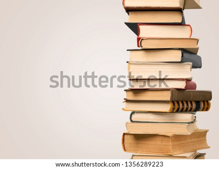 Collection of old books vertical stack on beige background #1356289223