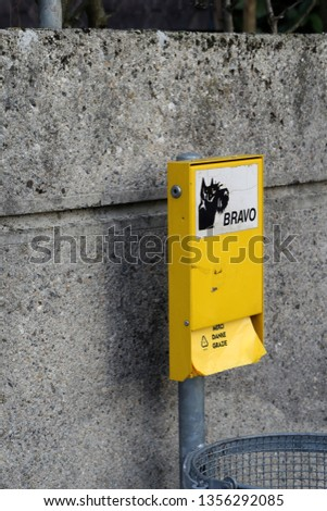 """March 2019 in Nyon, Switzerland. Yellow sign saying """"bravo"""" (=great) and offering dog waste bags that say thank you in many languages. Urban way to keep the city clean. Grey wall in the background.  #1356292085"""