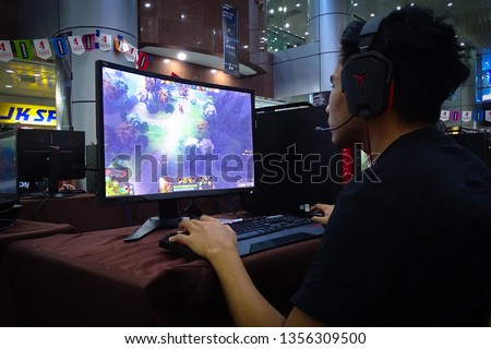 Labuan,Malaysia-March 29,2019:Young people playing video games Dota 2 in cyber cafe at Labuan,Malaysia.It is a multiplayer online battle arena video game developed & published by Valve Corporation. #1356309500