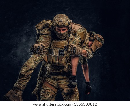 Combat conflict, special mission, retreat. Soldier special forces rescue his wounded teammate carrying him on his shoulders from the battlefield. Studio photo against a dark wall Royalty-Free Stock Photo #1356309812