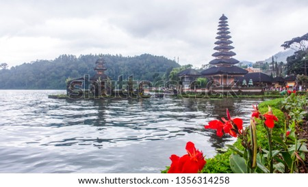 Bali, Indonesia - December 2017: Red Canna Lily flowers in front of Pura Ulun Danu Bratan water temple, with tourists. #1356314258