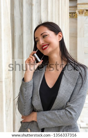 smiling woman is talking to the phone in front of marble column #1356337316