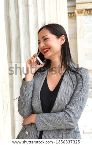 smiling woman is talking to the phone in front of marble column #1356337325