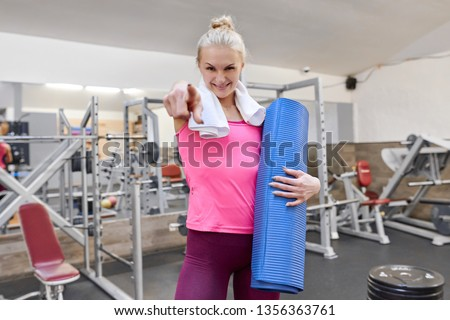 Young sporty blond woman pointing finger to you in gym. People fitness sport healthy lifestyle concept. #1356363761