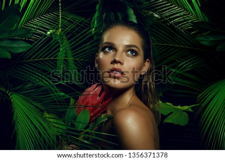 A beautiful tanned girl with natural make-up and wet hair stands in the jungle among exotic plants.fashion, beauty, makeup, cosmetics, beauty salon, style, personal care, posture, hair, hair. #1356371378