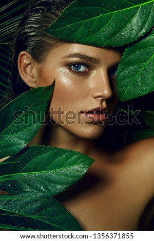 A beautiful tanned girl with natural make-up and wet hair stands in the jungle among exotic plants.fashion, beauty, health, ecology, makeup, personal care, hair, nature. #1356371855