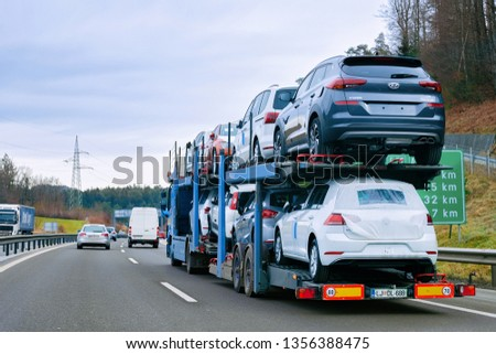 Ljubljana, Slovenia - January 16, 2019: Car carrier transporter truck on road. Auto vehicles hauler on driveway. European transport logistics at haulage work transportation. Heavy haul trailer #1356388475