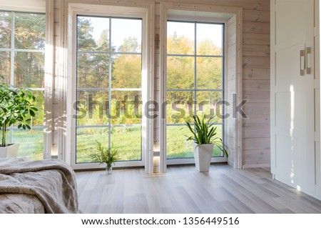 Bright interior, room in wooden house with large window. Scandinavian style. Royalty-Free Stock Photo #1356449516