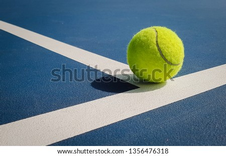 Close-up shots of yellow tennis balls On a tennis court with shadows caused by the light at the beautiful morning shining sun Warm with exercise #1356476318