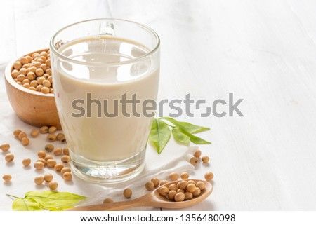 Soy or soya milk in a glass with soybeans in wooden bowl background #1356480098