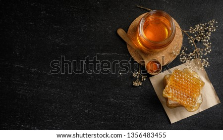 Honey bee and Honeycomb with honey dipper and dry flower on black background, bee products by organic natural ingredients concept #1356483455