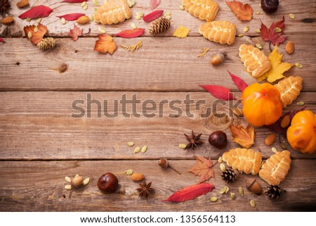 cookies and autumn leaves on old wooden background #1356564113