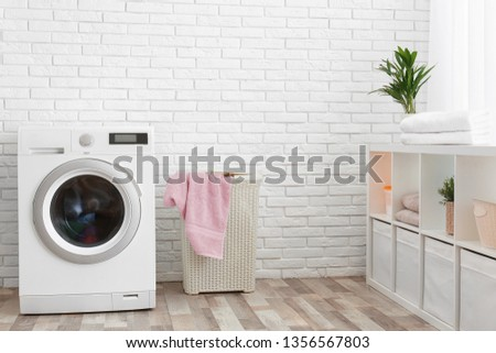 Modern washing machine near brick wall in laundry room interior, space for text #1356567803