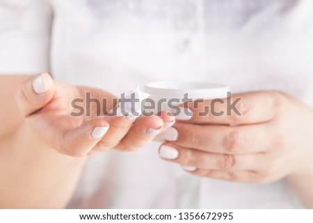 Adult woman applying hand cream, closeup #1356672995
