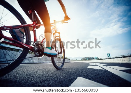 Woman cyclist legs riding Mountain Bike on highway #1356680030