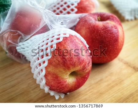 Fresh imported apples from a supermarket come with SINGLE-USE PLASTICS grocery bag and fruit foam net. Environmentalism & Plastic Awareness.- Close up #1356717869