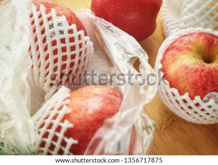 Fresh imported apples from a supermarket come with SINGLE-USE PLASTICS grocery bag and fruit foam net. Environmentalism & Plastic Awareness. - Close up #1356717875