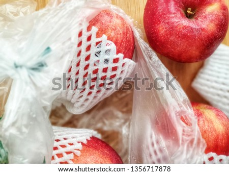 Fresh imported apples from a supermarket come with SINGLE-USE PLASTICS grocery bag and fruit foam net. Environmentalism & Plastic Awareness. - Close up #1356717878
