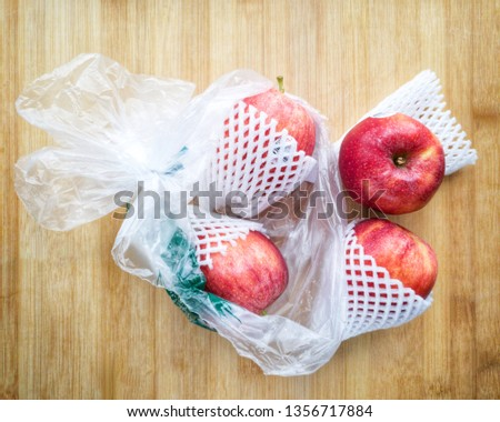 Fresh imported apples from a supermarket come with SINGLE-USE PLASTICS grocery bag and fruit foam net. Environmentalism & Plastic Awareness. #1356717884