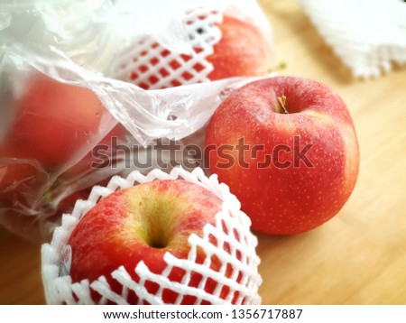 Fresh imported apples from a supermarket come with SINGLE-USE PLASTICS grocery bag and fruit foam net. Environmentalism & Plastic Awareness. - Close up #1356717887