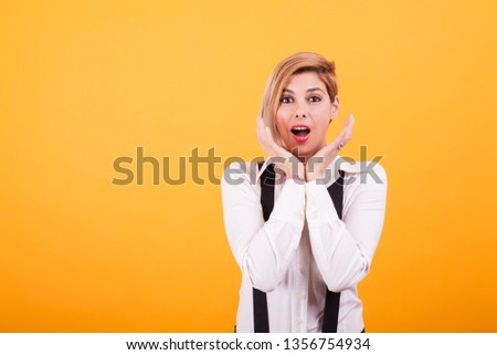 Attractive woman with blond hair looking shocked at camera over yellow background. Beautiful eyes. Facial expression. #1356754934