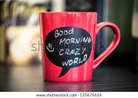 Red ceramic cup with good morning sign made with chalk. Standing on a kitchen table.