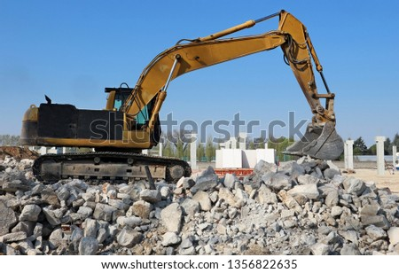 Excavator at work above a pile of debris in an industrial redevelopment area #1356822635