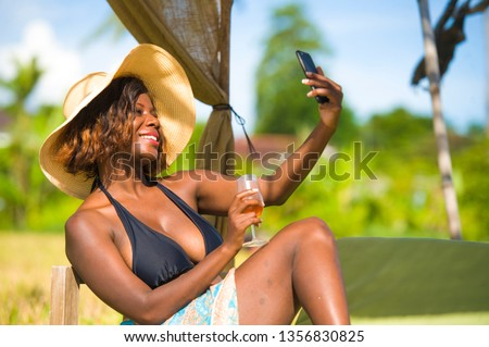 young happy and attractive black African American woman in bikini taking selfie picture with mobile phone for internet social media relaxed at tropical beach resort drinking glass of wine