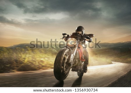 Speed of inspiration, aspiration and wild energy on the road. Get faster. Biker in black helmet is driving the handsome sport motorbike near meadows and mountains in cloudly evening on country side. #1356930734