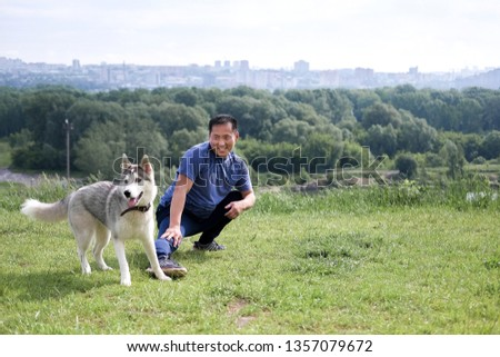 Korean man stretches against the background of the city. Healthy lifestyle. Adult man  practicing yoga in nature. #1357079672