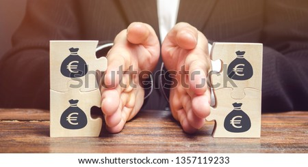 Businessman separates the wooden puzzle with a picture of money. The concept of financial management and distribution of funds. Saving and investing. Property division. Divorce and legal services