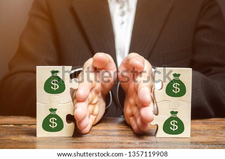 Businessman separates the wooden puzzle with a picture of money. The concept of financial management and distribution of funds. Saving and investing. Property division. Divorce and legal services #1357119908