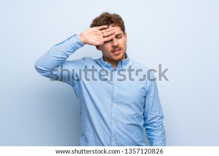 Blonde man over blue wall with tired and sick expression #1357120826