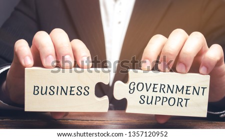 Businessman collects puzzles with the words Business and government support. Tax relief. Protection of manufacturers in the domestic market and promotion in foreign markets. Exemption from taxes. Royalty-Free Stock Photo #1357120952