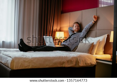 Manager takes a break, lays on the bed. Businessman relaxing in bed with a lap top beside him.  #1357164773