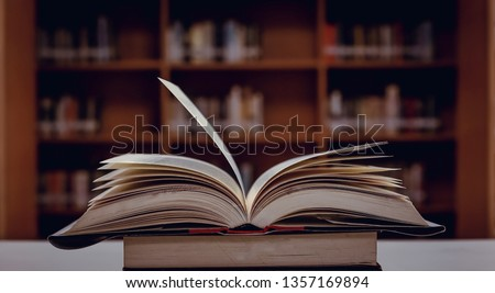 Stack of books in the library and blur bookshelf background #1357169894