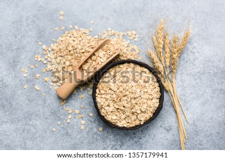 Rolled oats or oat flakes in bowl top view, concrete background. Healthy eating, dieting, weight loss concept #1357179941