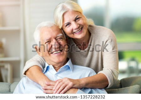 Portrait of happy senior couple sitting on sofa at home  #1357228232