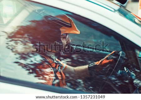 Rally driver, the man in the helmet tensely and seriously looking forward, side view through the car window at the racer participating in the rally, racing competition Royalty-Free Stock Photo #1357231049