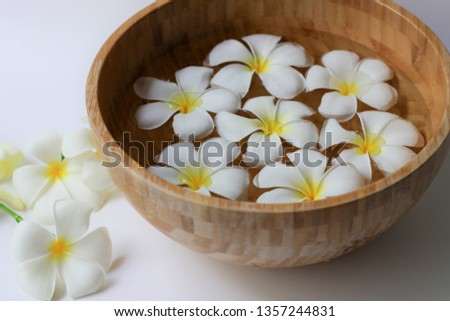 Spa composition, White flowers floating in a wooden bowl with water on white background #1357244831