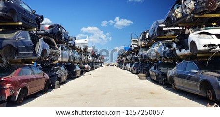 Old wrecked cars in junkyard waiting to be shredded in a recycling park  Royalty-Free Stock Photo #1357250057