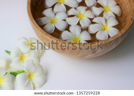 Spa composition, White Plumeria or Frangipani flowers floating in a wooden bowl with water on white background #1357259228