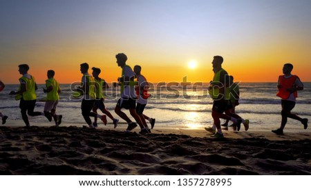 Durres, Albanie - circa Aug, 2017: The soccer team, coaching training running outdoor under the beach sunset, cinematic steadicam shot #1357278995