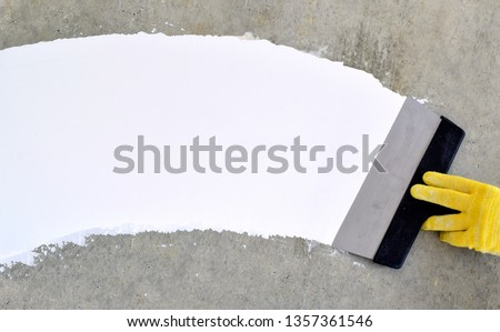 Hand with a spatula, the process of applying a layer of putty. Renovation of apartments. Repair the walls. Free space for advertising, text. #1357361546