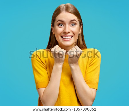 Young girl stares at camera with eyes full of happiness, holds hands clenched in fists. Photo of attractive girl in yellow sweater on blue background. #1357390862