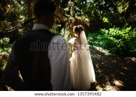 A wedding couple enjoys walking in the woods #1357395482