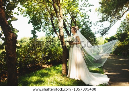 Beautiful bride walking in the park. Wedding veil disperse of wind. Beauty portrait of a bride around amazing nature #1357395488